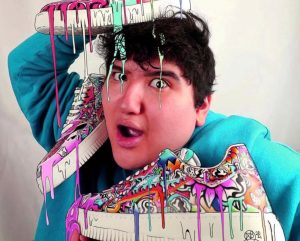 Wild eyed lad holding colorful sneakers