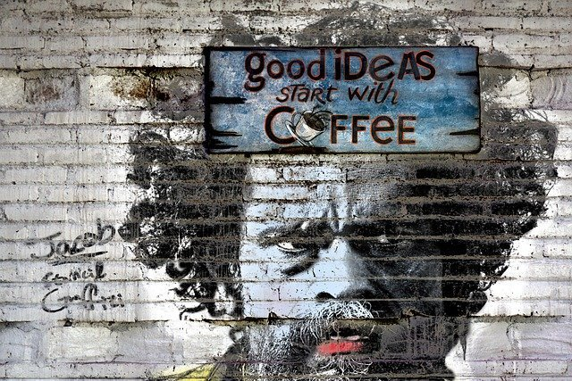 Image of Mans face in mural with great ideas start with coffee caption