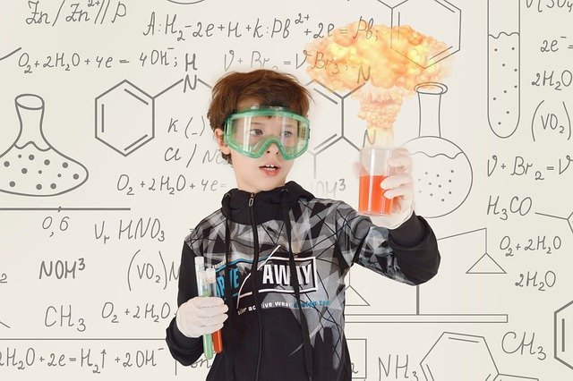 boy with beaker and colorful liquid in front of whiteboard with math equations